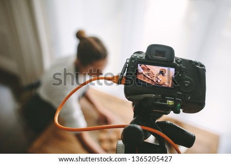 Food blogger recording video in kitchen, focus on camera display. Pastry chef making a new vlog on preparing dessert.