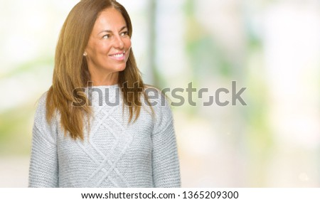 Beautiful middle age adult woman wearing winter sweater over isolated background looking away to side with smile on face, natural expression. Laughing confident. #1365209300