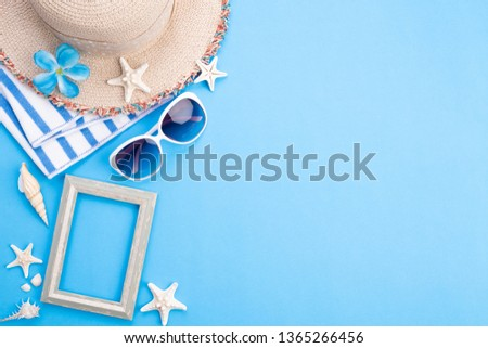 Beach accessories picture frame, sunglasses, starfish, beach hat and sea shell on blue background for summer holiday and vacation concept.