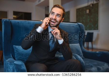 Handsome young businessman wearing suit sitting at the hotel lobby, using mobile phone #1365286256
