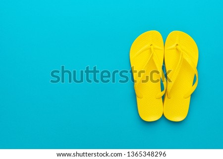 pair of yellow beach flip-flops on the blue background summer concept. minimalist flat lay photo of beach flip-flops with some copy space #1365348296