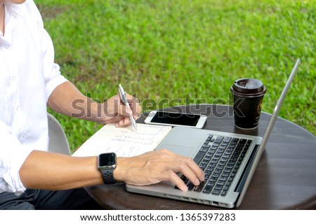 young buseness man work on the table with his laptop and coffee in garden outdoor loaction #1365397283