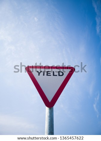 Yield road sign with blue sky and the word yield printed on it before a roundabout, Ireland.