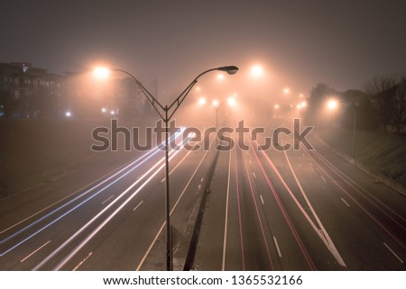 Highway at foggy night with bright trails of light from incoming and outgoing traffic. Transportation, traffic, urbanism and infrastructure concepts. #1365532166