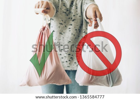 Ban single use plastic, stop sign. Choose plastic free. Zero Waste shopping concept. Woman holding in one hand groceries in reusable eco bag and in other vegetables in plastic polyethylene bag #1365584777