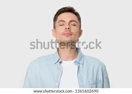 Calm young Caucasian male isolated on grey studio background enjoy pleasant smell or fragrance, relaxed European man in shirt breath deep, feel mindful inhaling fresh air. Stress free concept #1365602690
