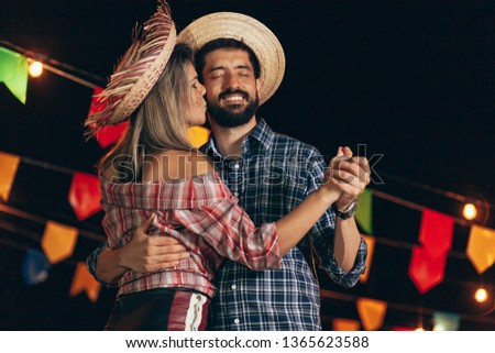 Brazilian couple wearing traditional clothes for Festa Junina - June festival - dancing under the night sky #1365623588