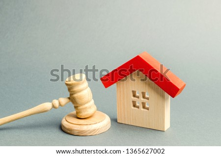 Miniature wooden house and judge's hammer. The concept of resolving property disputes. Property alienation. Confiscated housing. Nationalization. Services of a lawyer. Court. Gavel. Law #1365627002