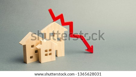 Miniature wooden houses and a red arrow down. The concept of low cost real estate. Lower mortgage interest rates. Falling prices for rental housing and apartments. Reducing demand for home buying #1365628031