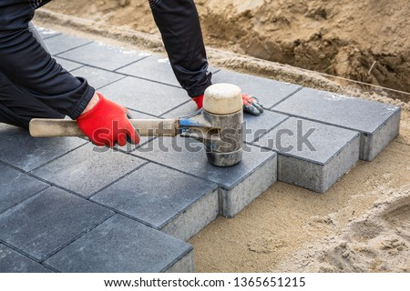 Hands of worker installing concrete paver blocks with rubber hammer #1365651215