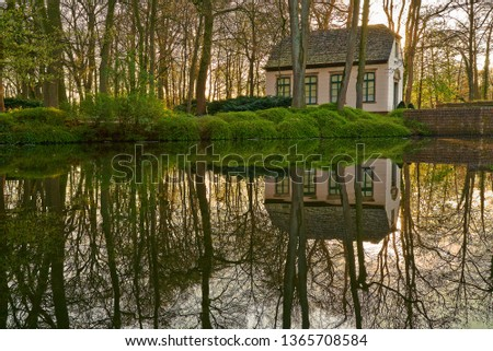 """historic house of the gardener in the public park called """"Graftanlagen"""" in Delmenhorst (Germany) surrounded by leafless trees romantically reflecting in the water of the river Delme during sunset Royalty-Free Stock Photo #1365708584"""