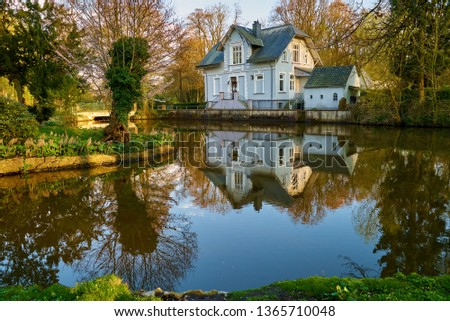 """old white house in traditional style reflects in the water of the moat in the public park called """"Graftanlagen"""" in Delmenhorst (Germany) during late afternoon on a sunny spring day with blue sky Royalty-Free Stock Photo #1365710048"""
