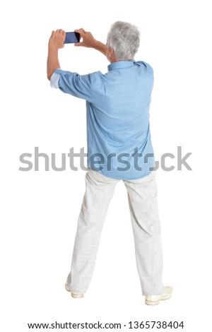 Portrait of senior man taking selfie on white background #1365738404