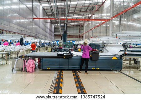 Industrial cloth cutting machine and fabric cutting area in garment factory in industrial zone in Ho Chi Minh City, Vietnam, with modern machinery and technology systems. Royalty-Free Stock Photo #1365747524