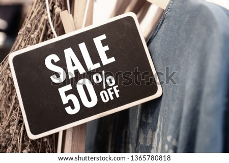 Sale 50% off Mock up wood black advertise display frame setting on clothes line at shopping department store fashion for shop, Business advertisement for customer concept. Vintage tone #1365780818