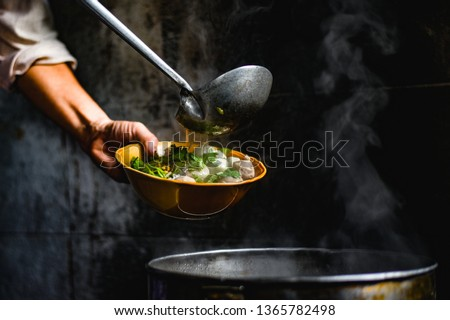 Hands of Thai Chef are scooping a delicious soup topped with noodles and pork balls in the corner of the restaurant with light shining to the noodle bowl that is traditional Thai food. #1365782498