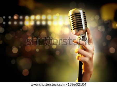 Female hand holding a single retro microphone against colourful background Royalty-Free Stock Photo #136602104