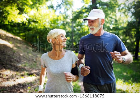 Fitness, sport, people, exercising and lifestyle concept - senior couple running Royalty-Free Stock Photo #1366118075