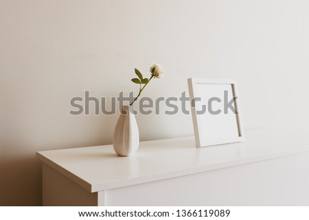 Close up of single rose in small white vase next to blank square picture frame on sideboard against neutral wall - warm matte filter effect and selective focus