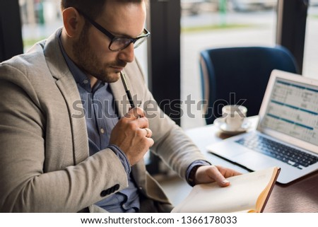 Serious businessman writing down memos while working computer in a cafe #1366178033
