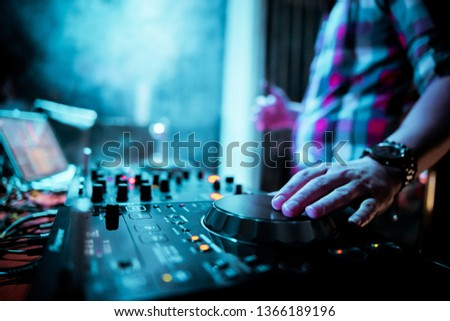 Night club, nightlife concept. DJ hands hold microphone and mixing DJ remote. Neon light #1366189196