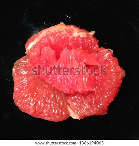 Food photo of citrus fruit grapefruit. In the photo, the grapefruit is peeled and sliced. Pulp of grapefruit on a black plate. #1366194065