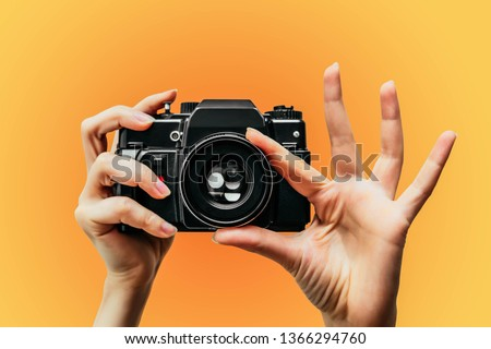 Vintage Camera in female hand. A photo. Photographer. Manual focus. Colored background. orange Royalty-Free Stock Photo #1366294760