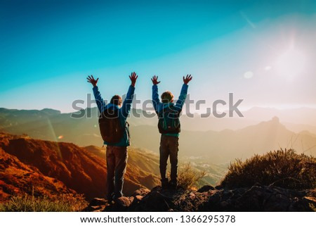 Happy father and son hiking at sunset mountains #1366295378