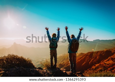 Happy father and son hiking at sunset mountains #1366295393