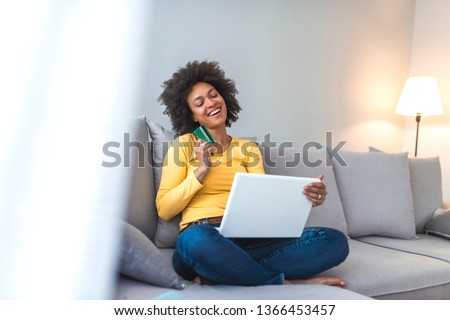 Mixed-race woman shopping on internet. Woman is holding credit card and using laptop computer. Online shopping concept. Picture showing pretty woman shopping online with credit card
