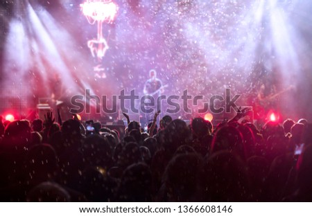 Crowd at concert - Cheering crowd in bright colorful stage lights #1366608146