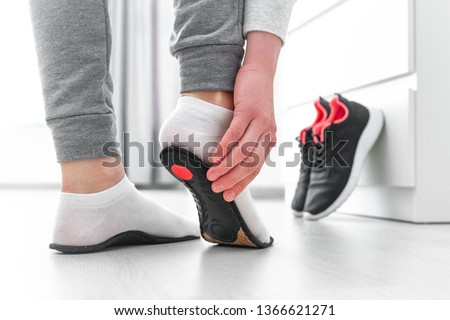 Sports woman fitting orthopedic insoles. Treatment and prevention of flat feet and foot orthopedic diseases. Foot care, feet comfort. Health care. Wearing sports comfortable shoes #1366621271