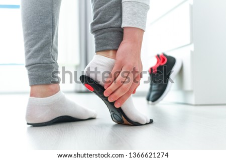 Sports woman fitting orthopedic insoles. Treatment and prevention of flat feet and foot orthopedic diseases. Foot care, feet comfort. Health care. Wearing sports comfortable shoes #1366621274