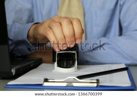 Man in business clothes puts a stamp on the documents in the office. Concept of official, custom officer, manager, permission, businessman, contract