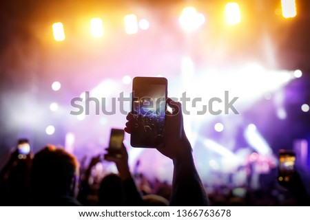 Hand with a smartphone records live music festival, live concert, live concert. #1366763678