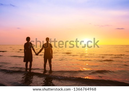Romantic couple on the beach at sunset watching horizon, honeymoon vacation holidays at sea destination, silhouette of two lovers holding hand #1366764968
