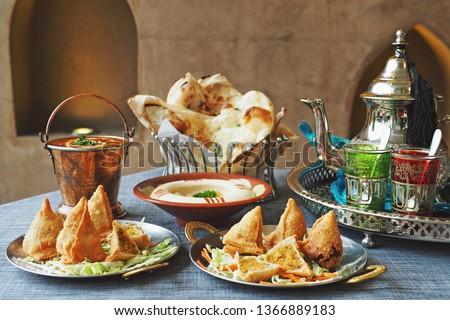 Halal chicken samosas and vegetable samosas with blurred dal makhani, hummus, naan bread, tea pot on the dining table. Ramadan food preparation for iftar meal during the holy month. (selective focus) #1366889183