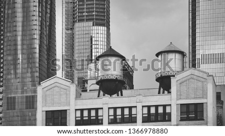 Black and white picture of a water tower s on a building rooftop, New York City, USA.