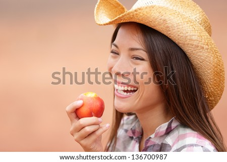 American cowgirl eating peach or nectarine fruit smiling and laughing wearing cowboy hat outside. Healthy eating concept with beautiful young mixed race Caucasian Asian female model outdoor.
