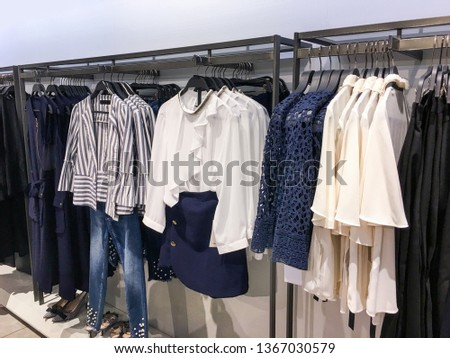female colorful clothing shoes, set of on the racks in clothing store #1367030579
