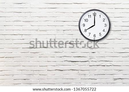 Wall clock on abstract white brick wall background. Office clock on white brick wall texture #1367055722