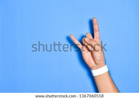 Top view close up of Men hand of posting rock with empty white wristband on colorful pastel on background view. Flat lay creative wallpaper. #1367060558