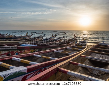 Colorful wooden fisher boat standing on the sandy beach in Senegal. Africa #1367103380