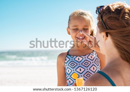 Young mother applying protective sunscreen on daughter nose at beach. Woman hand putting sun lotion on child face. Cute little girl with sunblock at seaside with copy space. #1367126120