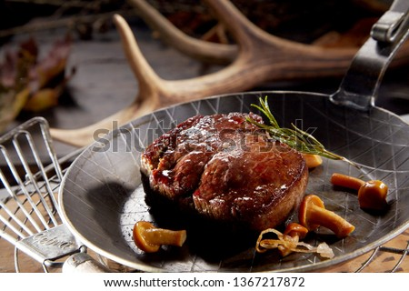 Thick juicy grilled wild venison steak served in a skillet with forest mushrooms and rosemary against a backdrop of shed antlers form deer #1367217872