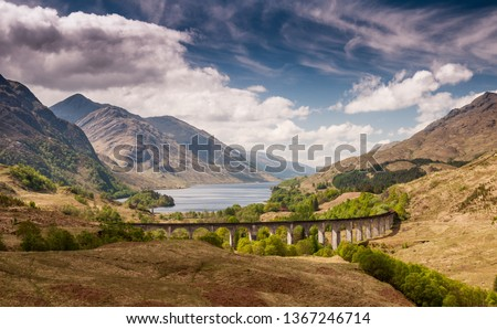 The Glenfinnan Viaduct carries the West Highland Railway Line high above Glen Finnan valley beside the lochs and mountains of Scotland. #1367246714