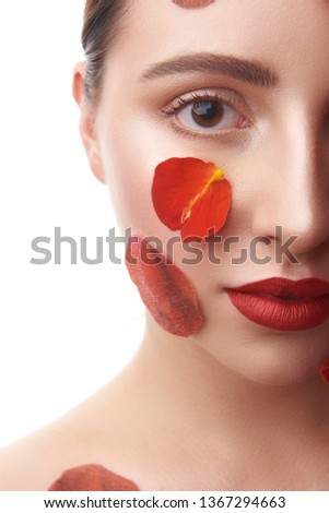 Beautiful woman looking at the camera and posing isolated on the white background with red lips and flower petals #1367294663