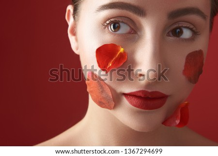 Beautiful young woman face with four rose petals on the cheeks isolated against the red background #1367294699