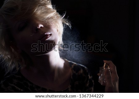 Woman puts on perfume on a dark background. #1367344229