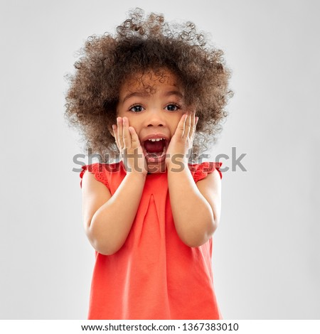 childhood and people concept - surprised or scared little african american girl screaming over grey background #1367383010